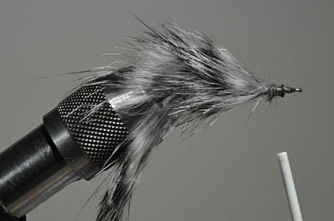 Einige Büschel Haar eines Zonkerstreifens abschneiden und hinter dem Hakenöhr einbinden. Abschlussknoten machen und den Bindefaden abschneiden.